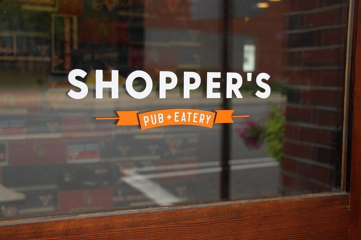 Shopper's Pub + Eatery Indian head Shoe Wall Interior Signage Window Sign with Interior Signage behind it